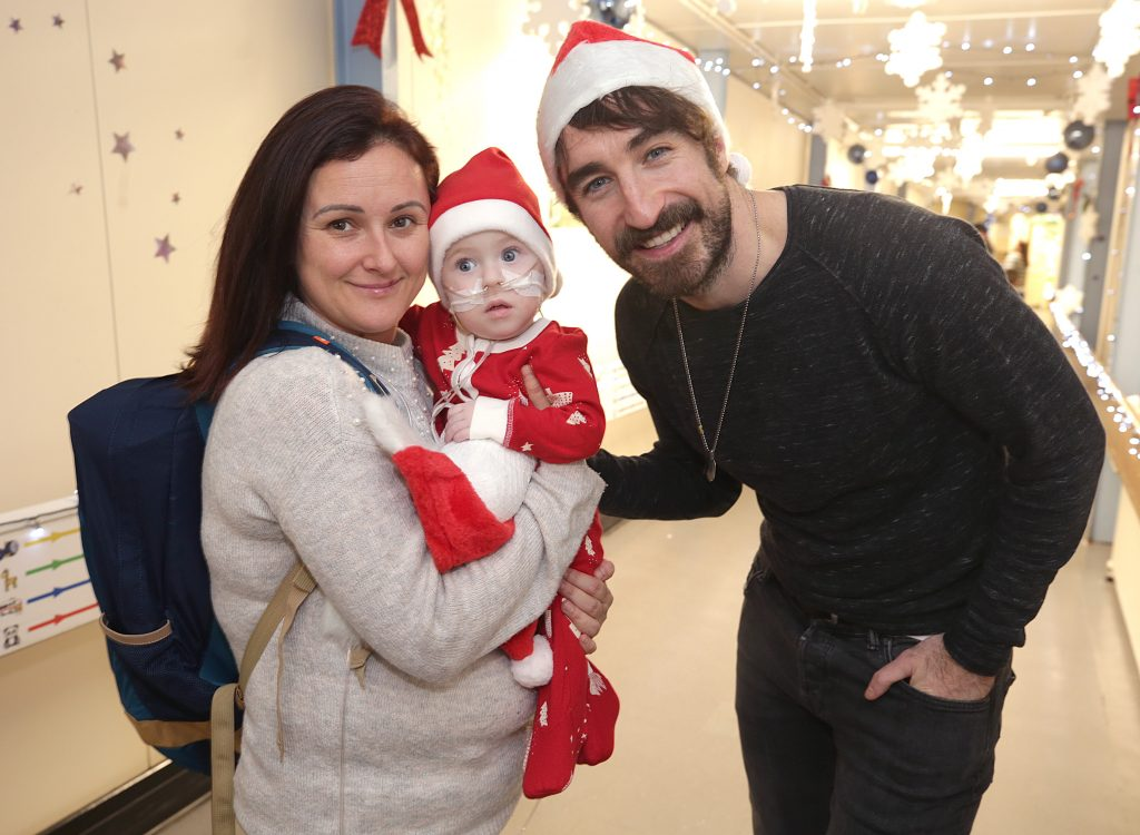 Jenny and her son Jake O'Donovan, aged 1, from Tralee Co. Kerry with Danny O'Reilly, lead singer of The Coronas, pictured before turning on the Christmas lights at Temple Street Children's Hospital in Dublin. Picture credit: Andres Poveda Photography